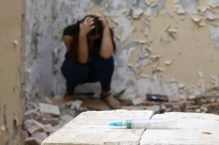 A drug-dependent woman suffers from drug withdrawal while sitting in abandoned building and dirty syringe for narcotic injections. Drug adiction problems concept Фото со стока