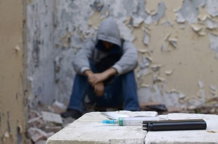 A drug-dependent man suffers from drug withdrawal while sitting in abandoned building and items for narcotic injections. Drug adiction problems concept