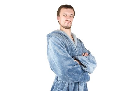 Portrait of young caucasian bearded proud man in blue bathrobe with crossed hands isolated on white background. Confident emotion concept