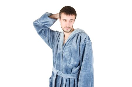 Portrait of young caucasian bearded man in blue bathrobe shows clueless emotion isolated on white background. Guilty facial expression concept