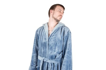 Portrait of young caucasian bearded man in blue bathrobe looking sideways with a tired look isolated on white background. Bored emotion concept 写真素材