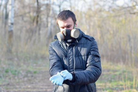 Portrait of young man in protective gas mask wears rubber disposable gloves outdoors in spring wood. Concept of protective goods usage during quarantine 写真素材