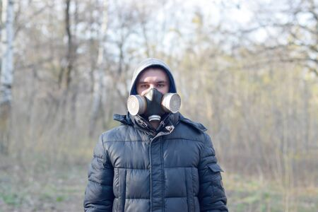 Portrait of young man in protective gas mask outdoors in spring wood. Concept of protective goods usage during quarantine 写真素材