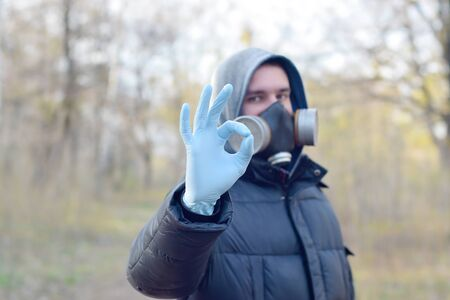 Portrait of young man in protective gas mask and rubber disposable gloves shows okay gesture outdoors in spring wood. Concept of protective goods usage during quarantine