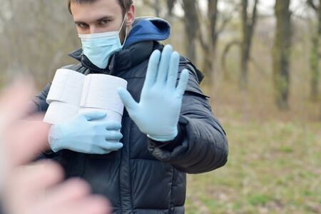 Covidiot concept. Young man in protective mask holds many rolls of toilet paper and shows stop gesture outdoors in spring wood. Panic buying during quarantine