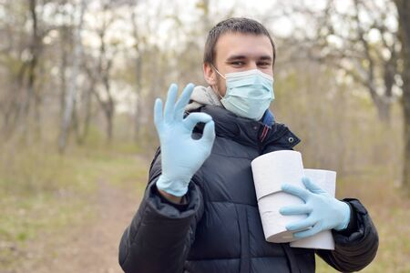 Covidiot concept. Young man in protective mask holds many rolls of toilet paper and shows okay gesture outdoors in spring wood. Panic buying during quarantine 写真素材