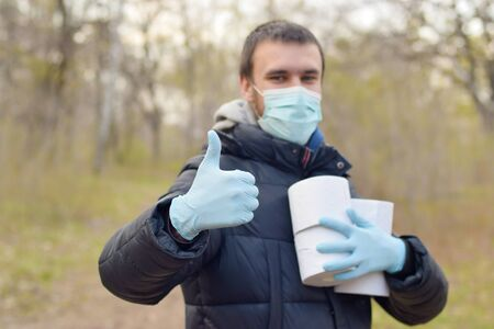 Covidiot concept. Young man in protective mask holds many rolls of toilet paper and shows thumb up outdoors in spring wood. Panic buying during quarantine