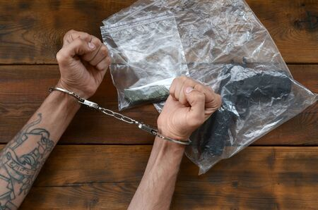 Handcuffed hands of criminal suspect on wooden table and crime scene evidence in transparent plastic packs for investigation. Handgun and jackknife