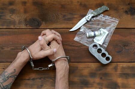 Cuffed hands of tattooed criminal suspect and plastic ziplock packet of evidence for investigation. Dirty money bills with jackknife and brass knuckle