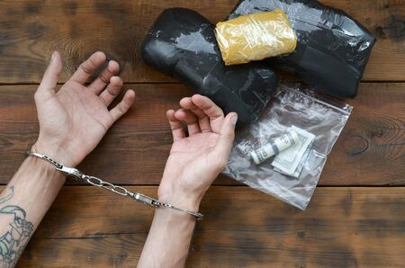 Drug trafficker arrested with their heroin packages. Police arrest drug dealer with handcuffs and narcotic packages on wooden table. FIght with drug selling