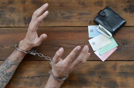 Cuffed hands of tattooed criminal suspect of carding and fake credit cards with cash in purse as evidence for investigation. Above view to old prison wooden table
