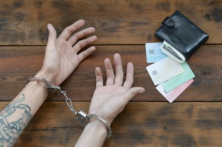 Cuffed hands of tattooed criminal suspect of carding and fake credit cards with cash in purse as evidence for investigation. Above view to old prison wooden table Banque d'images