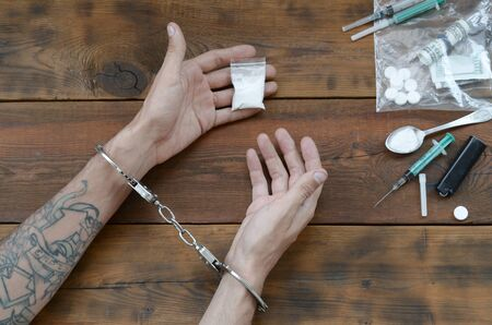 Drug traffickers were arrested along with their heroin. Police arrest drug dealer with handcuffs. Law and police concept for world anti drug day. 26 June, International day against drug abuse.