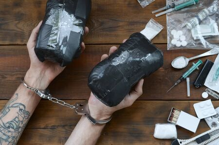 Drug trafficker arrested with their heroin packages. Police arrest drug dealer with handcuffs and many narcotic stuff on wooden table. 26 June International day against drug abuse. Stock Photo