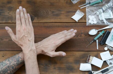 Male hands show NO sign to all of narcotic stuff definitions. Many drug pills and powder on wooden table. Fighting with drug abuse and dealing
