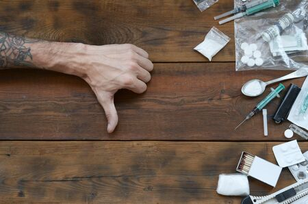 Male hands show dislike sign to all of narcotic stuff definitions. Many drug pills and powder on wooden table. Fighting with drug abuse and dealing