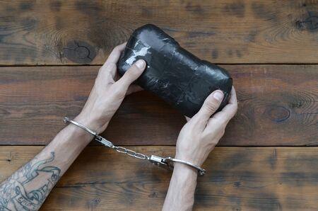 Arrested drug dealer hands in police handcuffs with big heroin drug package on dark wooden table background. Illegal drug trafficking concept. Fighting with drug sellers
