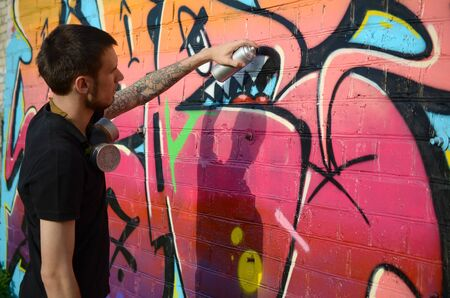 Young graffiti artist with backpack and gas mask on his neck paints colorful graffiti in pink tones on brick wall. Street art and contemporary painting process. Entertainment in youth subculture 写真素材