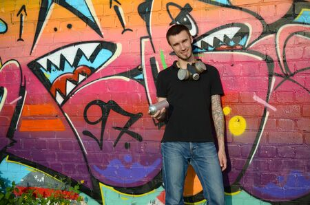 Young caucasian graffiti artist in black t-shirt with aerosol spray can near colorful pink graffiti on brick wall. Street art and contemporary painting process. Entertainment in youth subculture