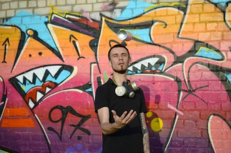Young graffiti artist with gas mask on his neck throw his spray can against colorful pink graffiti on brick wall. Street art and contemporary painting process. Entertainment in youth subculture 写真素材