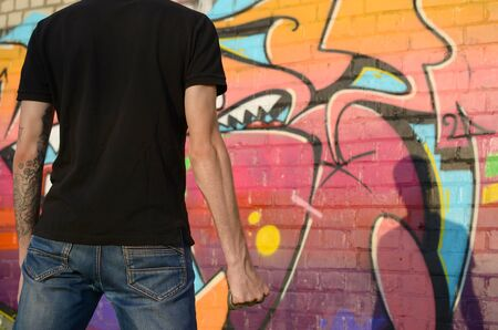 Back view of young caucasian man with brass cnuckle on his hand against ghetto brick wall with graffiti paintings. Concept of criminal forces and aggression charge. Classic gangsters melee weapon