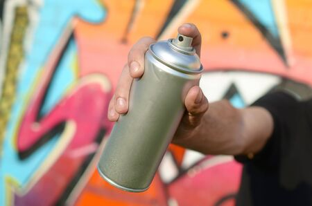 Young graffiti artist aims his spray can on background of colorful graffiti in pink tones on brick wall. Street art and contemporary painting process. Entertainment in youth subculture