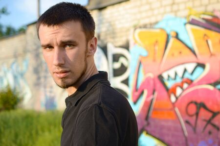 Portrait of young caucasian graffiti artist in black t-shirt near colorful pink graffiti on brick wall. Street art and contemporary painting. Entertainment in youth subculture 写真素材