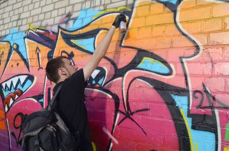 Young graffiti artist with backpack and gas mask on his neck paints colorful graffiti in pink tones on brick wall. Street art and contemporary painting process. Entertainment in youth subculture