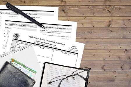 USCIS form I-90 Application to replace permanent resident card lies on flat lay office table and ready to fill. U.S. Citizenship and Immigration services paperwork concept. Top view