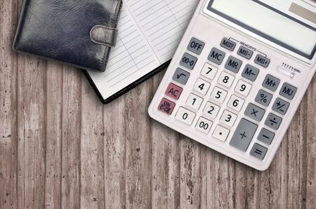 Office flat lay composition with big calculator, address book and black purse on brown wooden table background with top view. Accountant paperwork concept