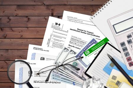 IRS form W-9 Request for taxpayer identification number and certification lies on flat lay office table and ready to fill. U.S. Internal revenue services paperwork concept. Time to pay taxes