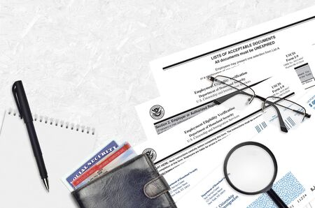 USCIS form I-9 Employment eligibility verification lies on flat lay office table and ready to fill. U.S. Citizenship and Immigration services paperwork concept. Top view Foto de archivo