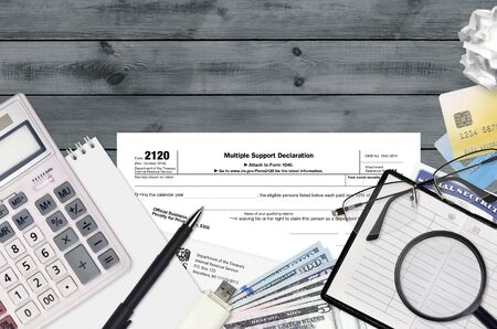 IRS form 2120 Multiple support declaration lies on flat lay office table and ready to fill. U.S. Internal revenue services paperwork concept. Time to pay taxes in United States. Top view Archivio Fotografico