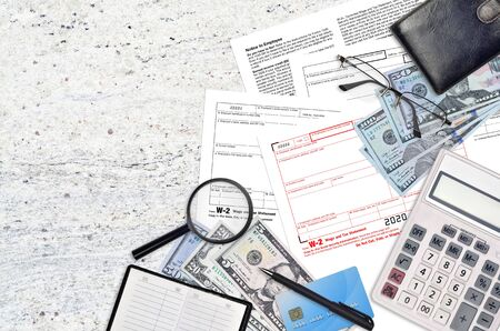 IRS form W-2 wage and tax statement lies on flat lay office table and ready to fill. U.S. Internal revenue services paperwork concept. Time to pay taxes in United States. Top view Foto de archivo