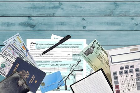 IRS form 1040 U.S. Individual income tax return with refund check lies on flat lay office table and ready to fill. U.S. Internal revenue services paperwork concept. Time to pay taxes in United States
