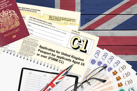 English form C1 Application for United Kingdom passport for applicants aged 16 or over lies on table with office items. UK passport paperwork process