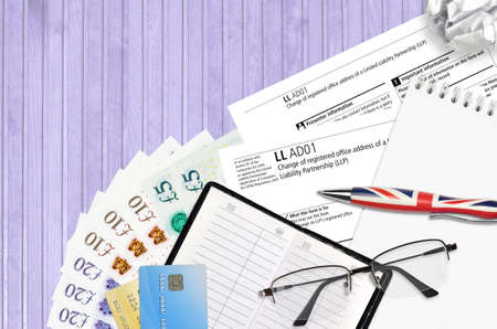English form LLAD01 Change of registered office address of a limited liability partnership LLP from Companies House service lies on table with office items. CH business and paperwork process