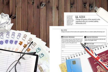 English form LLAD04 Change of location of the records to the registered office of a limited liability partnership LLP from Companies House service lies on table with office items. CH paperwork process Stock fotó