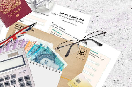 English Tax form sa103 Self-employment from HM revenue and customs lies on table with office items. HMRC paperwork and tax paying process in United Kingdom of Great Britain