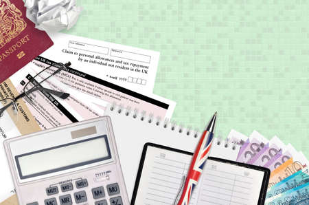 English Tax form R43 Claim to personal allowances and tax repayment by an individual not resident in the UK lies on table with office items. HMRC paperwork