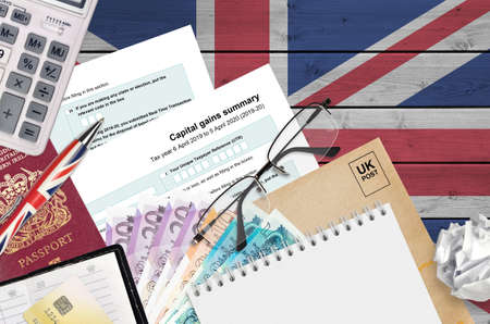 English Tax form sa107 Capital gains summary from HM revenue and customs lies on table with office items. HMRC paperwork and tax paying process in United Kingdom of Great Britain