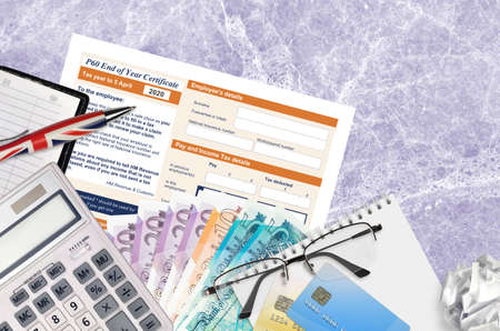 English Tax form P60 End of year certificate by HM revenue and customs lies on table with office items. HMRC paperwork and tax paying process in United Kingdom of Great Britain
