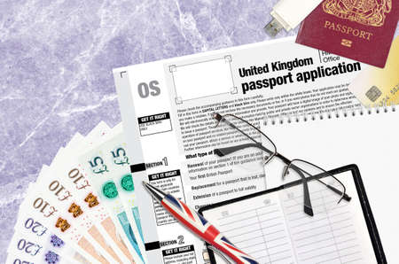 English form OS United Kingdom passport application from HM passport office lies on table with office items. UK passport paperwork process