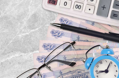 50 russian rubles bills and calculator with glasses and pen. Business loan or tax payment season concept. Financial planning and time to pay taxes