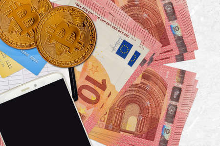 10 euro bills and golden bitcoins with smartphone and credit cards. Cryptocurrency investment concept. Crypto mining or trading transactions