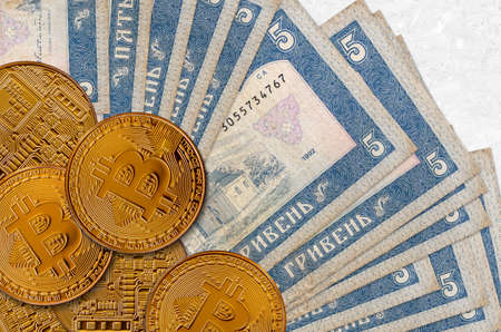 5 Ukrainian hryvnias bills and golden bitcoins. Cryptocurrency investment concept. Crypto mining or trading transactions