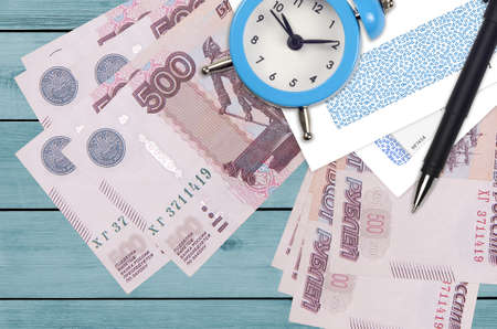 500 russian rubles bills and alarm clock with pen and envelopes. Tax season concept, payment deadline for credit or loan. Financial operations using postal service. Quick money transfer