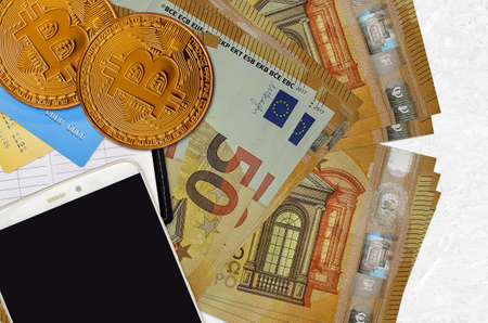 50 euro bills and golden bitcoins with smartphone and credit cards. Cryptocurrency investment concept. Crypto mining or trading transactions