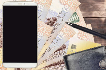 100 Ukrainian hryvnias bills and smartphone with purse and credit card. E-payments or e-commerce concept. Online shopping and business with portable devices usage