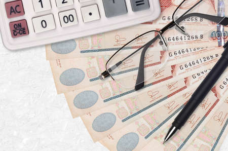 100 Guatemalan quetzales bills fan and calculator with glasses and pen. Business loan or tax payment season concept. Financial planning